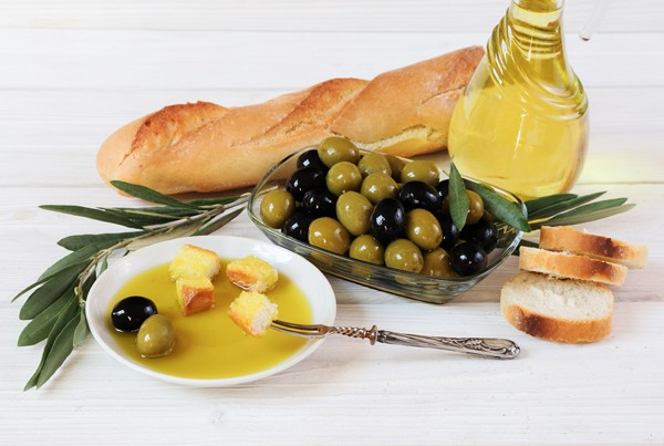 Olives, olive oil and bread on the wooden table